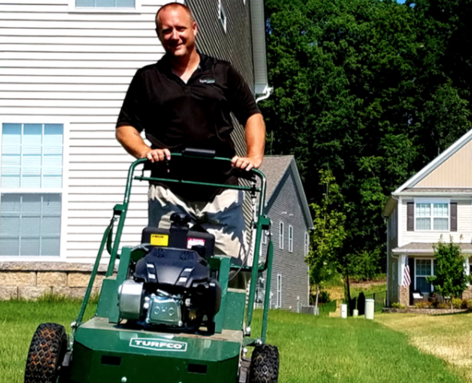 Charlotte ExperiGreen technician pushing lawn aeration machine