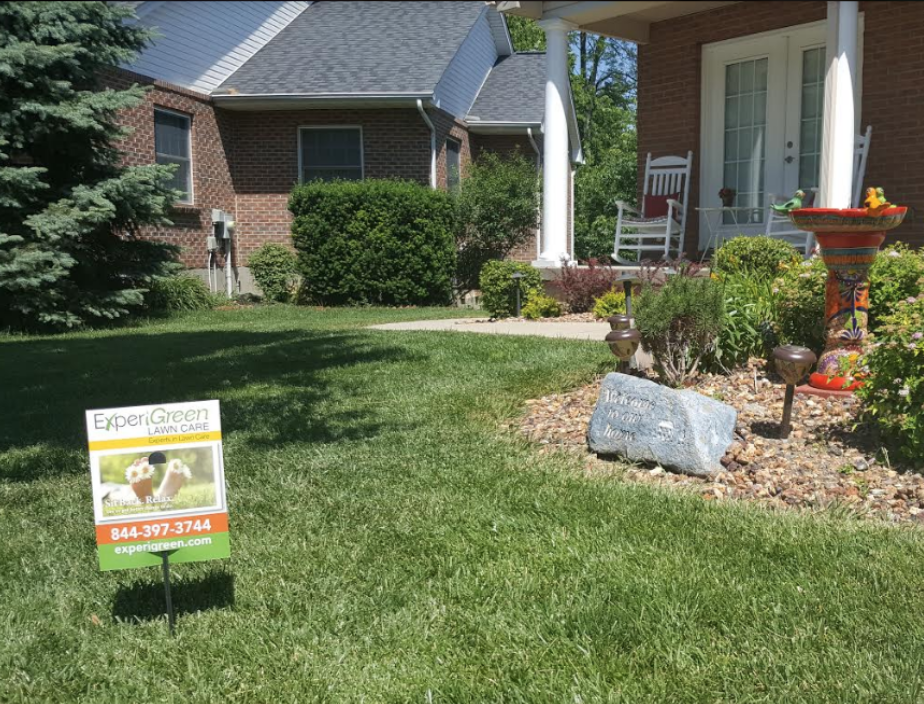 ExperiGreen sign on green lawn with nice landscaping and birdbath