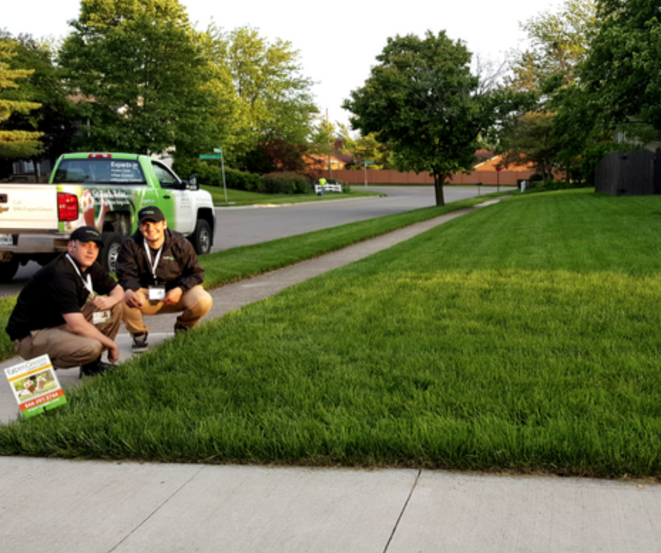 ExperiGreen technicians show off a green lawn they service